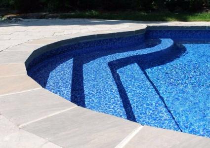 Vinyl over steel in-pool stair cantilevered brick coping